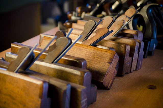 A row of antique wood molding planes sitting on a woodworking workbench