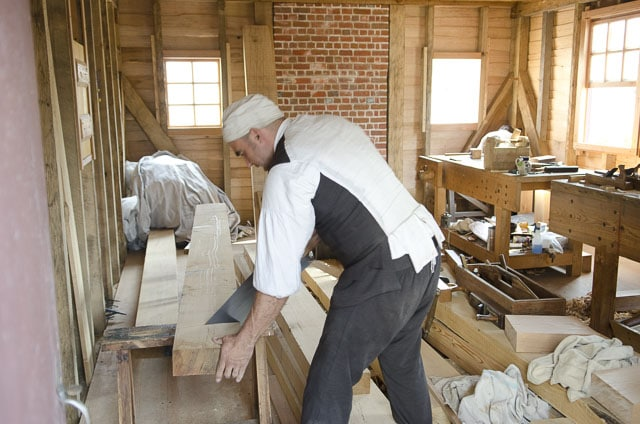 A Traditional Woodworker Uses A Hand Saw To Cut A Thick Board On A Saw Bench In A Colonial Williamsburg Woodworking Workshop