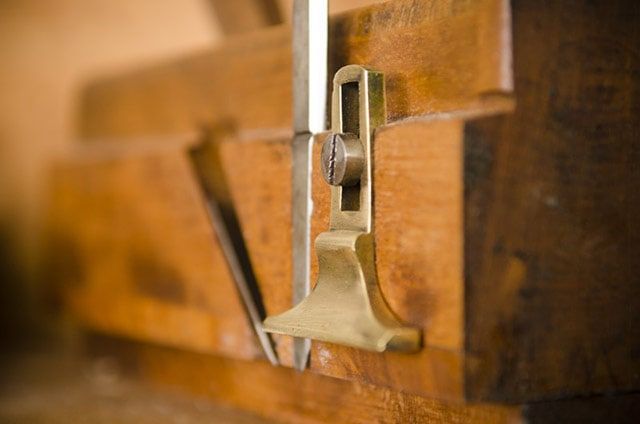 Closeup of wood plane called moving fillister plane with nicker and brass depth stop
