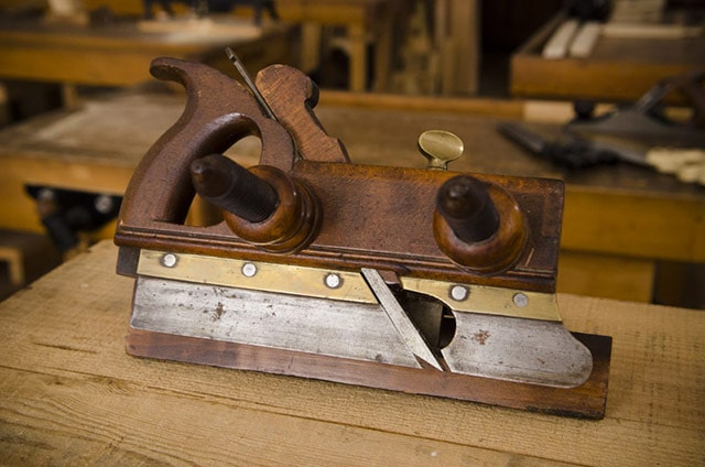 Wood Plane: Antique screw arm plow plane on a woodworking workbench in Roy Underhill's Woodwright's School