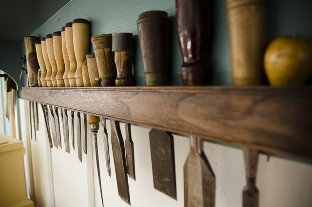 Wood chisel set hanging on a walnut tool shelf