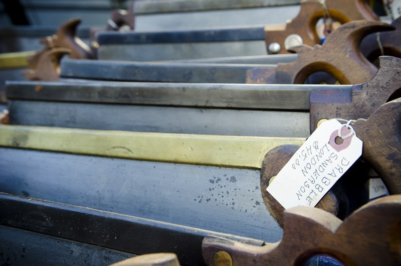 Row of antique back saws with price tags at a Midwest tool collector's meeting
