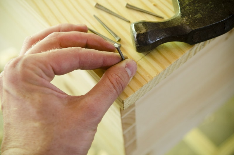 Woodworker Holding A Historical Style Cut Nail For Hammering A Wooden Desk Top