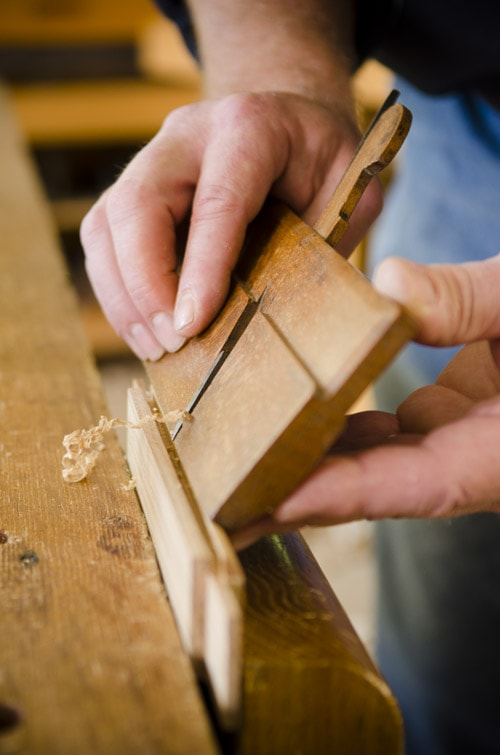 Woodworker Using A Round Hollow Molding Plane On A Door Frame With Woodworking Hand Tools