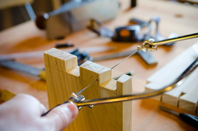 Coping saw cutting dovetail pins on woodworking workbench