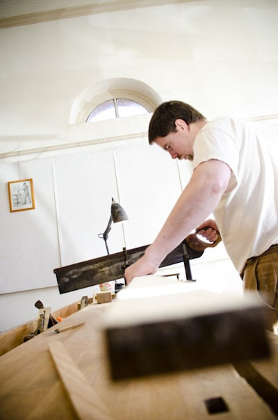 Woodworker using a miter box saw on a woodworking workbench in Roy Underhill's Woodwright's School