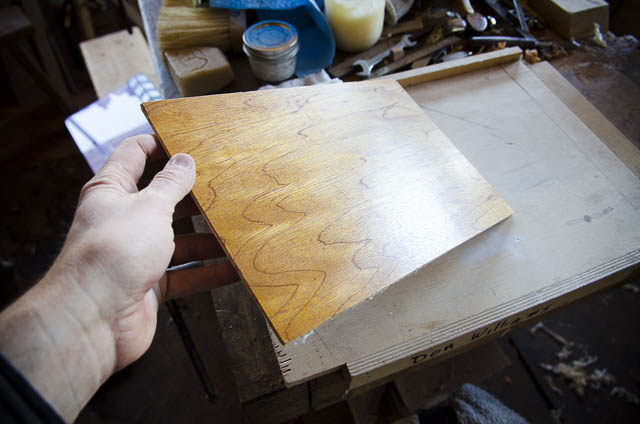 Don Williams holding a board rubbed with beeswax wood polish and French Polissoir or polisher