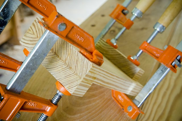 Gluing up a southern yellow pine bench hook with orange bar clamps on a woodworking workbench