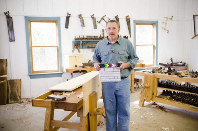 Will Myers holding a clapper board slate on set while filming a DVD about making a collapsiable trestle table in Joshua Farnsworth's woodworking workshop