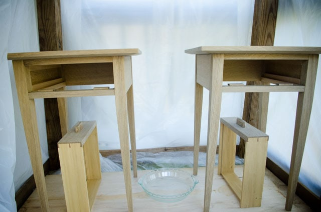 Two night stand end tables in a plastic ammonia fuming tent