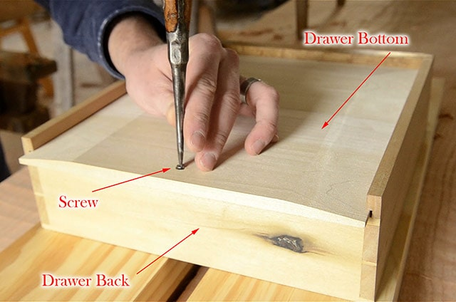 Diagram showing parts of a table drawer with hand using screwdriver to insert screw in drawer bottom