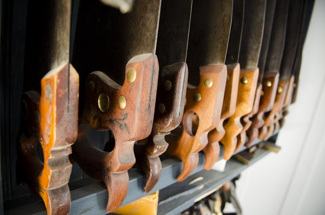 antique hand saws on a blue saw till