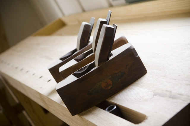 coffin smoother hand planes sitting on a woodworking workbench