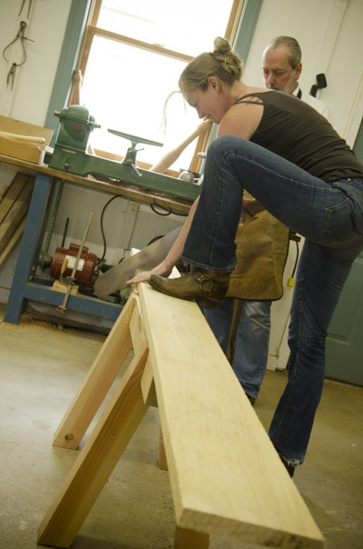 A female woodworking student using an antique crosscut panel saw with her boot on top to cut a board with woodworking lathe in the background