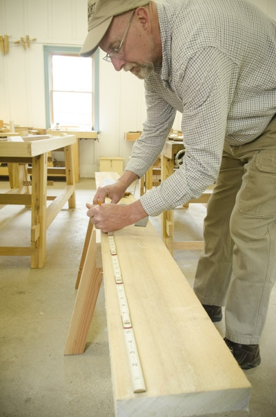 An older woodworking student using an antique zig zag rule ruler to measure a board on a saw horse