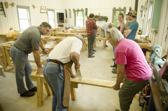 Woodworking students using an antique crosscut panel saw to cut a board with woodworking workbenches in the background