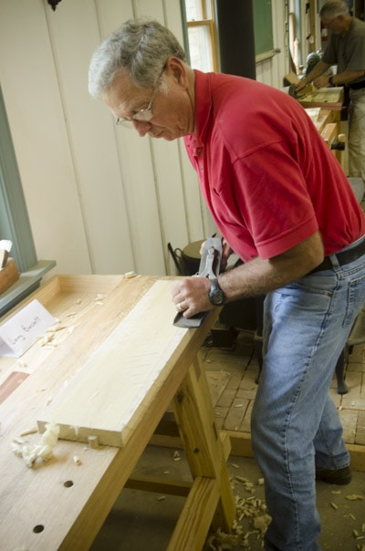 An older male woodworking student using an antique Stanley 7 jointer plane to flatten a board at a woodworking workbench