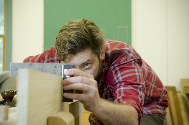 An bearded woodworking student checking a board with a try square at a woodworking workbench