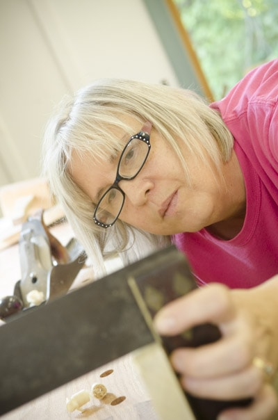 An older female woodworking student checking a board with a try square at a woodworking workbench