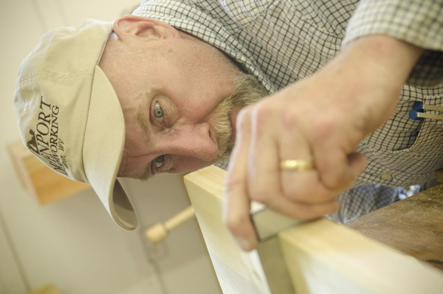 An older male woodworking student checking a board with a try square at a woodworking workbench