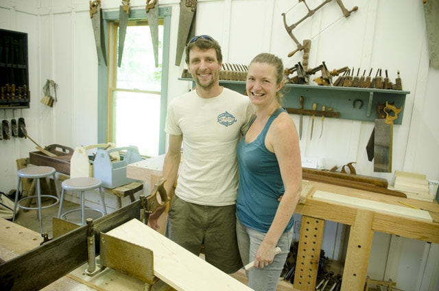 A young couple taking a woodworking class at the Wood And Shop traditional woodworking school surrounded by woodworking workbenches