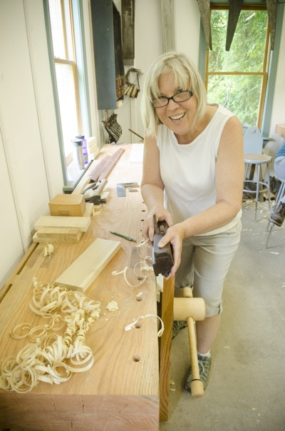 An older female woodworking student using a come and go tongue and groove plane at a Roubo workbench