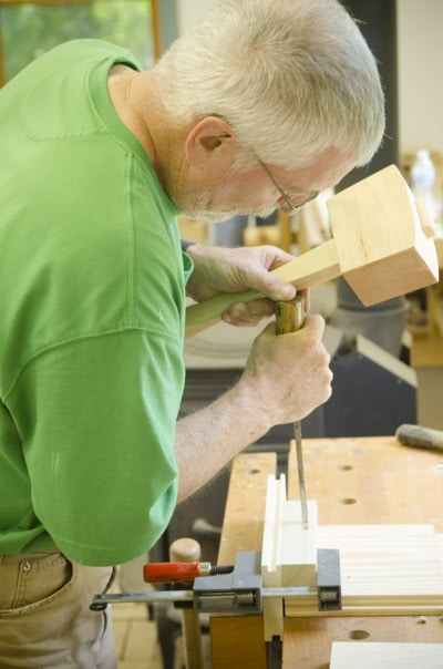 An older woodworker chopping a mortise and tenon joint with a joiner's mallet and mortise chisel