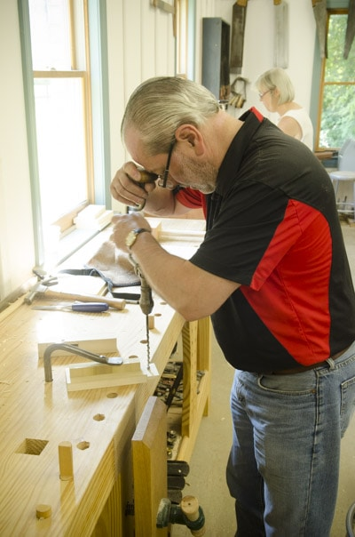 An older male woodworking student using an antique brace and bit to bore a hole in a tenon and mortise joint