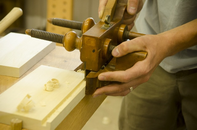 Closeup view of an antique wooden plow plane cutting a groove in a board