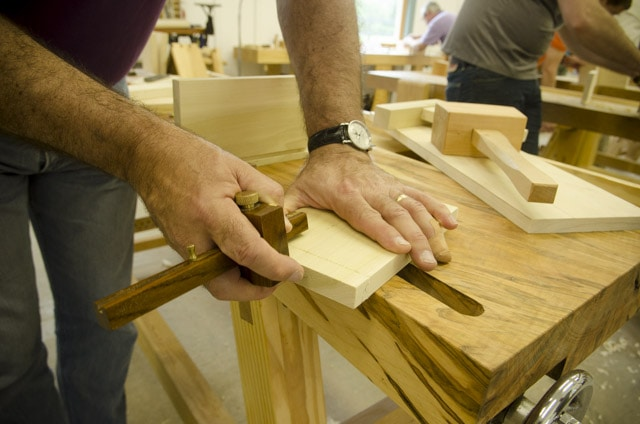 A male woodworking student using a mortise gauge to layout dovetail joints