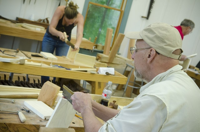 An older woodworking student using a dovetail saw to cut dovetail joints with a female woodworker cutting dovetails in the background
