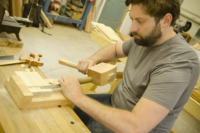 Bearded woodworking student using a chisel and joiner's mallet to cut a dado joint