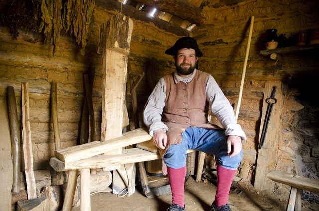 colonial man sitting on a woodworking shaving horse at the Frontier Culture Museum