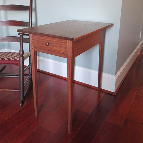 Canterbury shaker side table made by Will Myers sitting next to a shaker rocking chair