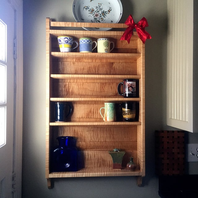Figured maple wall dish cabinet with Christmas bow by Dave Heller
