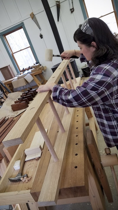 Woman using a mallet to fit an oak ladder together