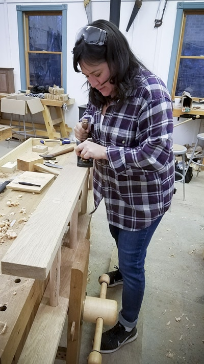 Lady using a hand plane on an oak ladder