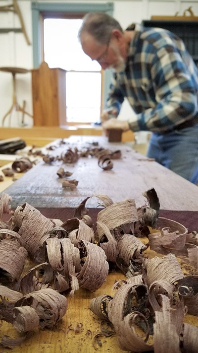 older man using a hand plane to flatten a board with shavings in the foreground