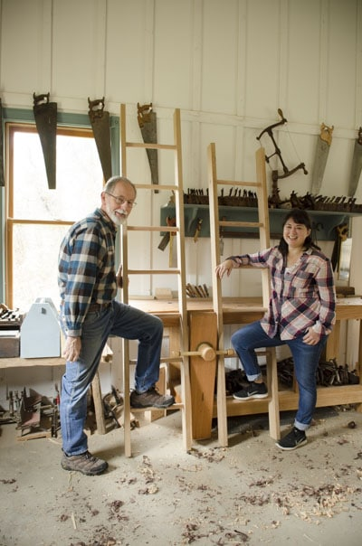 older man and lady holding onto ladders they just built with woodworking workbench in back