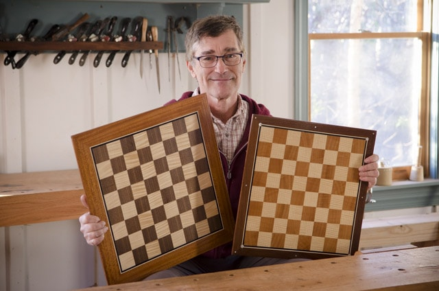 Dave Heller holding two veneered and inlaid chess boards