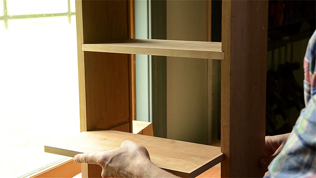 Shelves inserted into dado joints of a hanging shaker wall cupboard