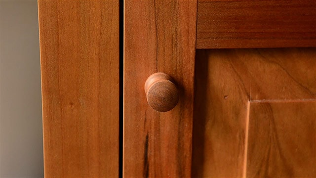 Cherry Shaker knob on a frame and panel door of a cupboard