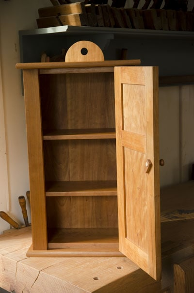 Cherry hanging shaker wall cupboard with door open showing shelves built by Joshua Farnsworth