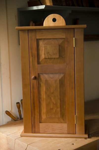 Cherry hanging shaker wall cupboard with door closed built by Joshua Farnsworth