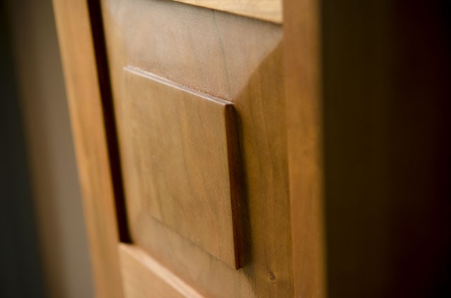 Door panel of a cherry hanging shaker wall cupboard built by Joshua Farnsworth