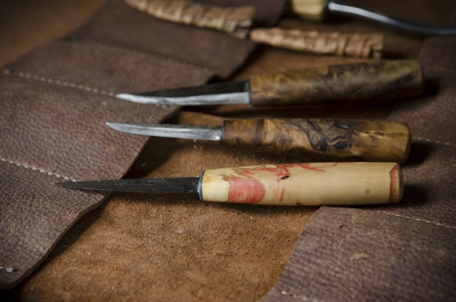 Green woodworking carving knives on a leather tool roll