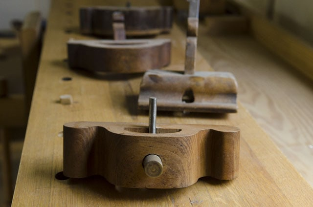 Antique wooden router planes sitting in a row on a woodworking workbench