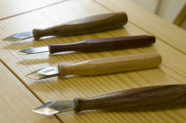 Cheap marking knives for woodworking sitting on a wooden tool chest