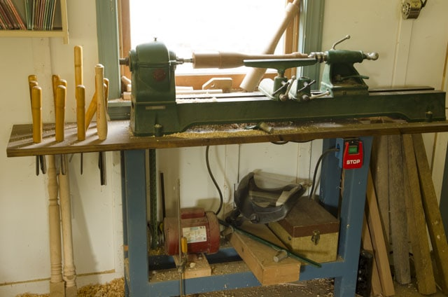 Tauco brand antique wood lathe on a custom made blue wooden base with wood turning tools hanging