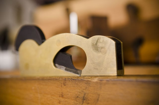 Small shoulder plane by Lie-Nielsen sitting on a woodworking workbench